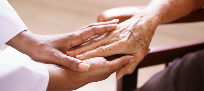 A carer places their hand on an older person's hand.